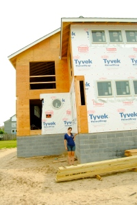 Allie stands next to a new home construction in Lewes, Delaware that is building up on several feet of freeboard.