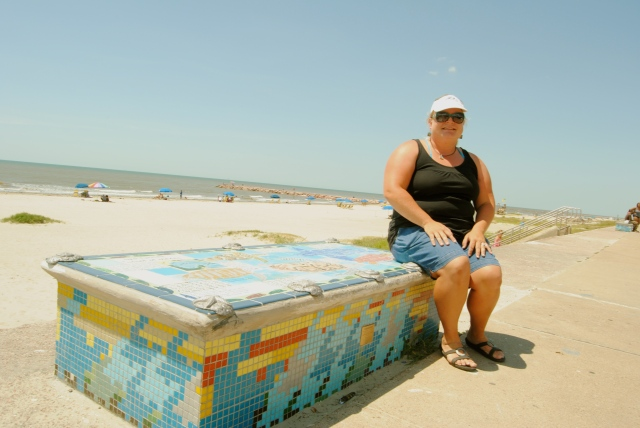 At Galveston's busiest public beach, along the town seawall, 1st and 2nd grade children worked with Artist Boat to paint educational mosaics about local sea life on public benches. Kari Howard sits on one of these works of art and environmental education.
