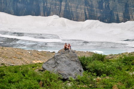 Allie Goldstein and Kirsten Howard atop a rock in front of Grinnell Glacier, which is retreating (melting) quickly.