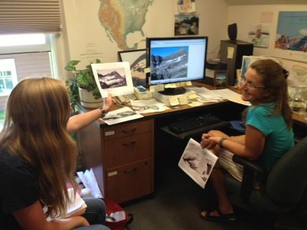 Road tripper Kirsten Howard and Lisa McKeon of USGS compare historical photos of glaciers with current ones.